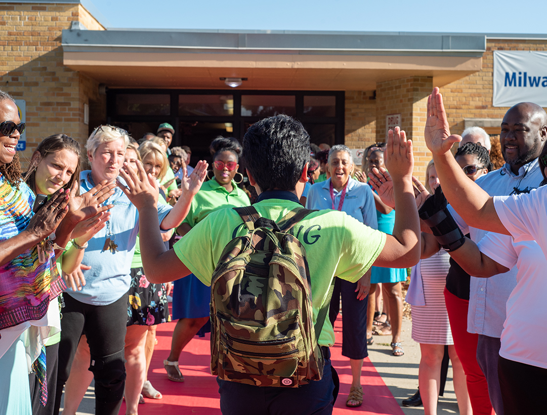 scholar walking the red carpet on the first day, high-fiving the staff